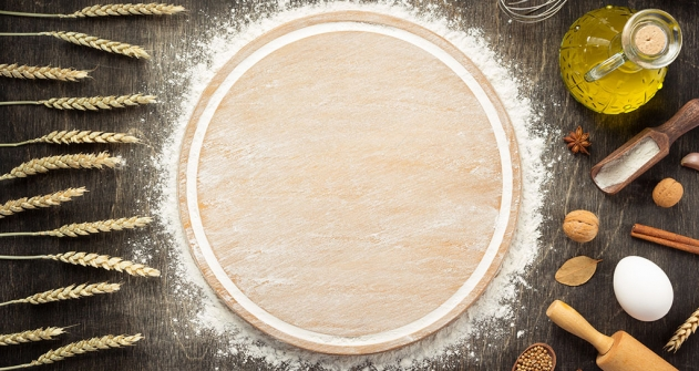 wheat flour and bakery ingredients on wooden background, top view